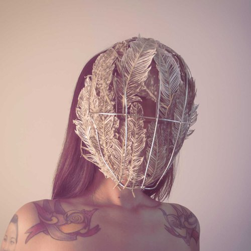 Wearable metal artwork in the form of mask made from copper and wire.