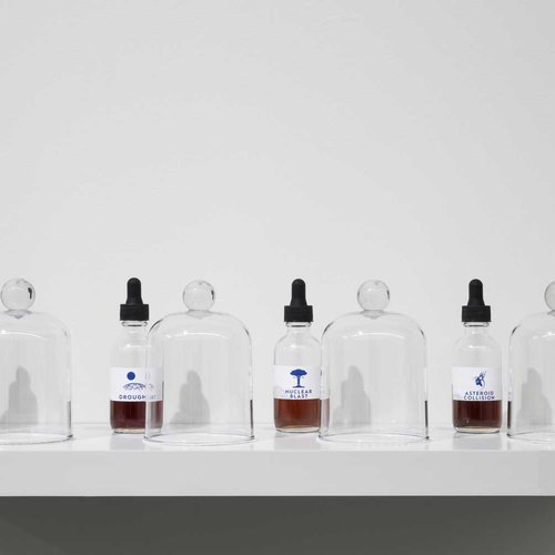 Display of four glass bottles with molecularly formulated scents on white shelf.
