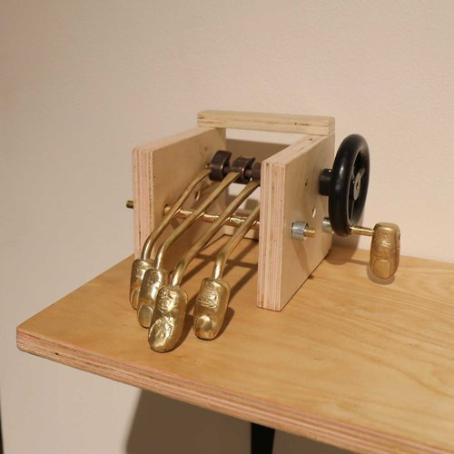 Mechanical artwork in wood and brass that mimics moving fingers.