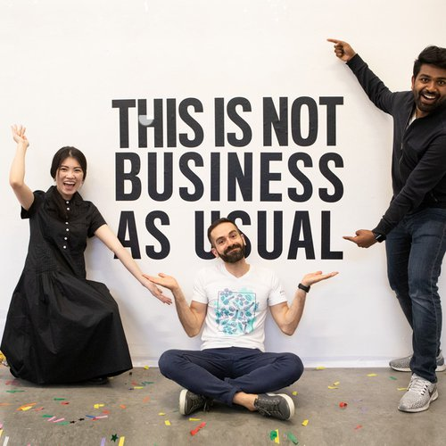 "Three students pose for a photo in front of a wall that says, ""This is not business as usual."""