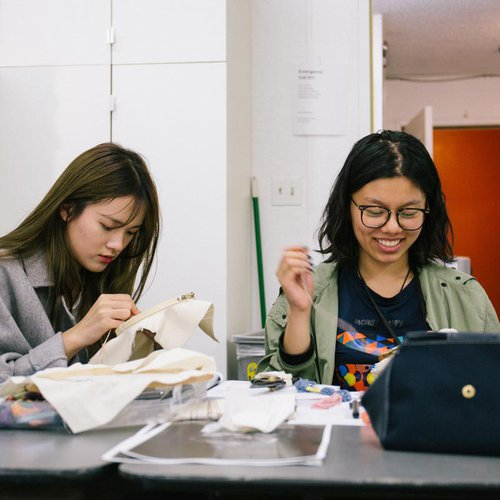 Two students practice stitching side by side.