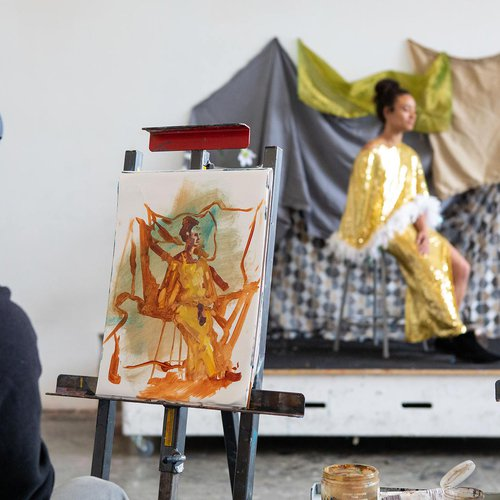 A student paints a seated model.