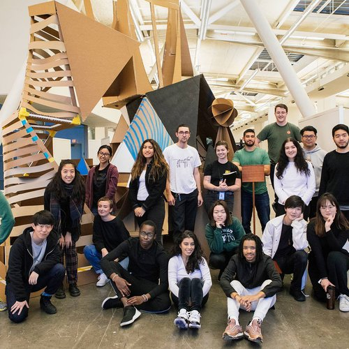 A group of students pose in front of a large-scale, mixed-media installation in the Nave.