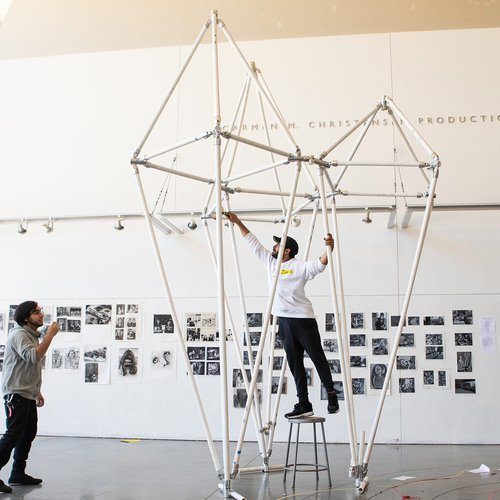 Two students construct a large-scale structure in the Nave.