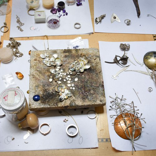 Curtis Arima's studio table with various metals, gems, bits of assemblage and pencil sketches on paper.