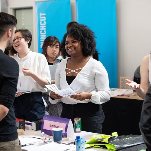 A student talks to a recruiter at a career expo event.