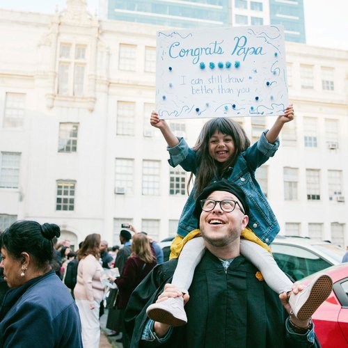 A child sits on her graduating father's shoulders while holding a silly sign congratulating him.