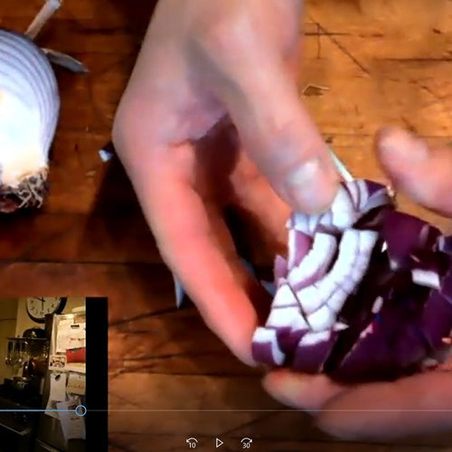 Arima cutting red onion for Chicken Tikka Masala with an overhead view of the kitchen via zoom.