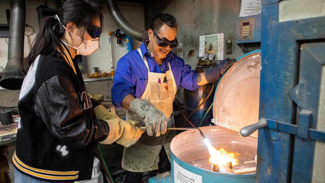 Curtis Arima showing a student how to work with metal castings