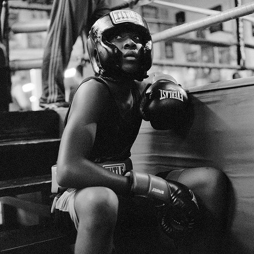 Young boxer sitting on a bench at the boxing gym.