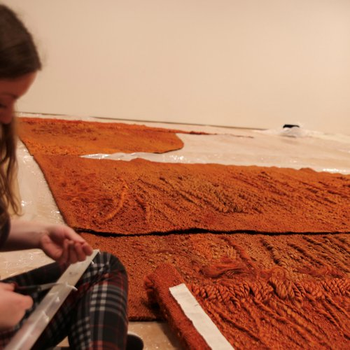 Claire Taggart at Nasher Sculpture Center, working on a large weaving by Magdalena Abakanowicz.