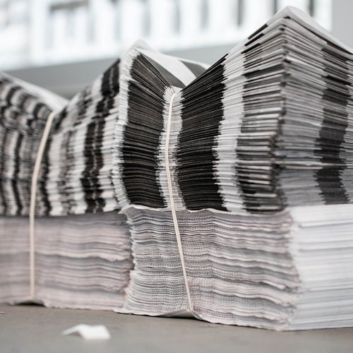 Stacks of printed newsprint compose the layered background of the on-site installation.