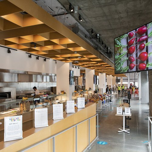 Interior view of Makers Cafe, an open kitchen and grill on the left and TV screen with a photo of beets above on the right.