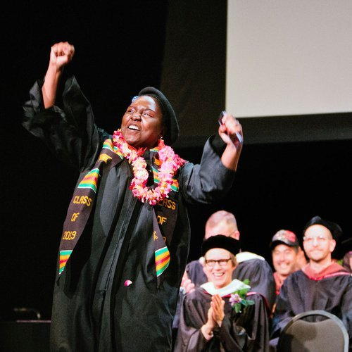 A graduating student celebrates on stage.