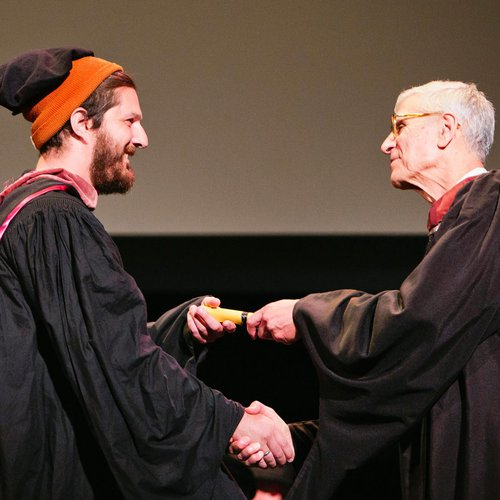 President Stephen Beal shaking a graduating student's hand.