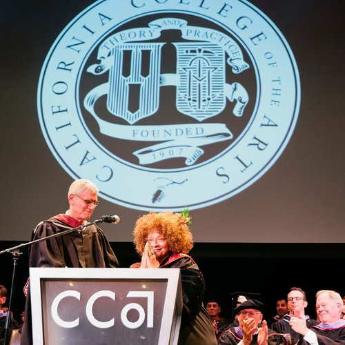 Joyce J. Scott and Stephen Beal share a laugh on the graduation stage.