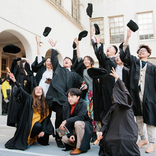 A group of graduating students throw their caps into the air.