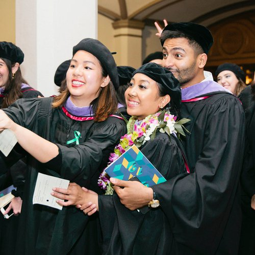 Students posing for a fun group selfie at their graduation ceremony.