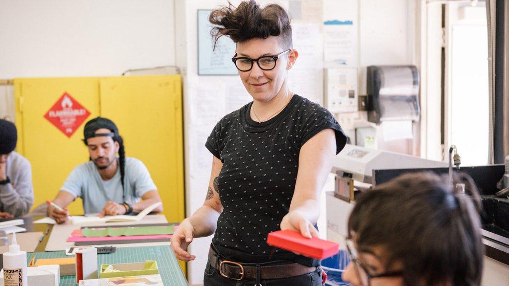 Book Arts Teacher handing something to student