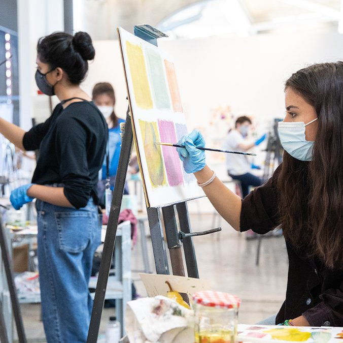 A close-up of two students painting using easels in a studio.