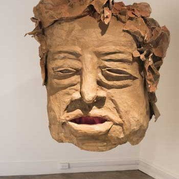 Giant head made from papier-mâché and mixed media.