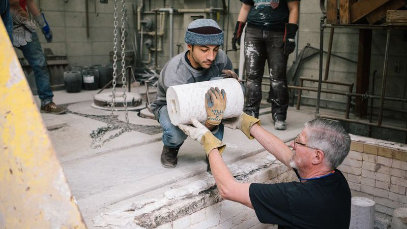 Faculty helps student lift their bronze cast sculpture