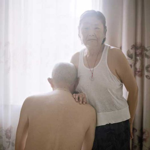Old man leans against an old woman in a moment of domestic intimacy.