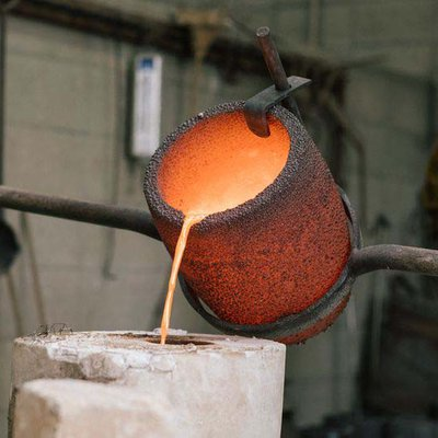 Poured liquid bronze in the metal foundry during advance sculpture