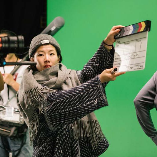 Film student shoots a take in the green screen film cage_hero image_MB