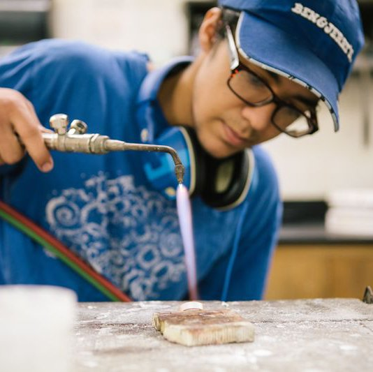 Jewelry and Metal Working student using a torch to mold their ring