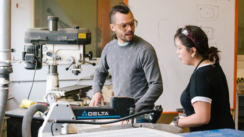 Shop manager helping a student safely use equipment in the woodworking studio_feature_MB