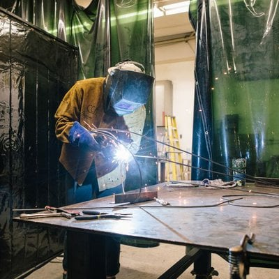 Student welding a sculpture during a metal working class